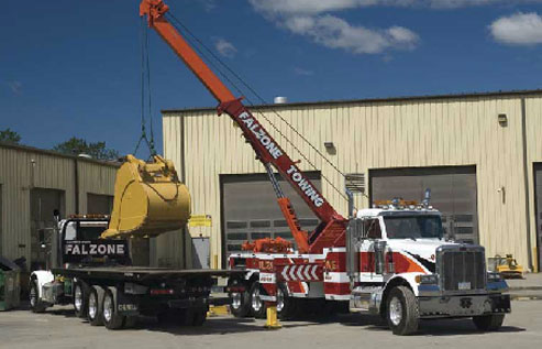 truck with a crane lifting a backhoe scoop