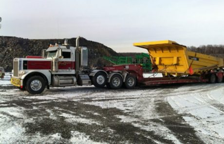 tow truck moving a large dump truck bed