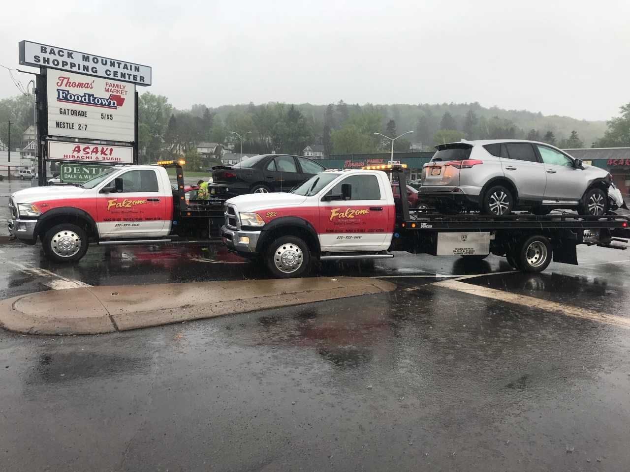 truck hauling car away from a wreck