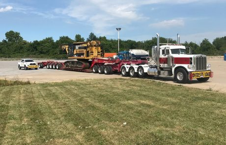 Large tow truck transporting construction equipment