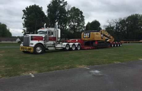 Tow truck carrying large construction equipment